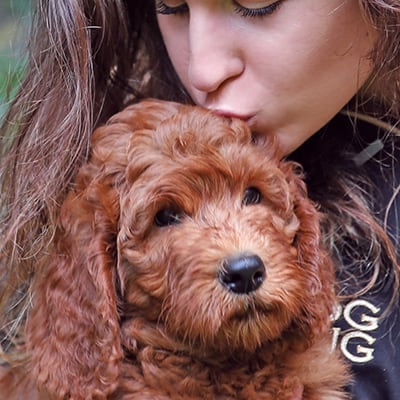 woman kissing a puppy